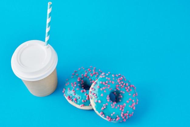 Xícara de café e rosquinhas sobre fundo azul, vista superior