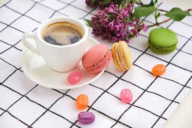 Xícara de café e saborosos macarons doces com caramelo e pirulitos coloridos