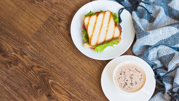 Xícara de café e sanduíche grelhado com guardanapo na mesa de madeira