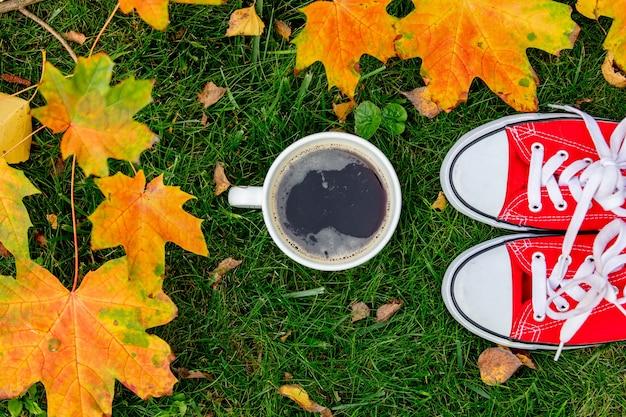 Xícara de café e sapatos desportivos vermelhos com folhas de bordo em uma grama verde em um jardim