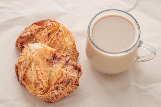 Xícara de café e scones em papel amassado marrom