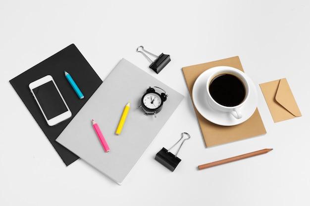 Xícara de café e smartphone, bloco de notas close-up vista superior
