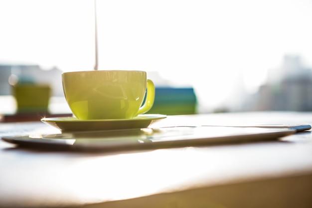 Xícara de café e tablet pc em uma mesa