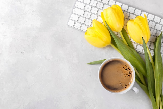 Xícara de café e teclado de tulipas amarelas