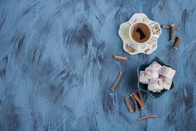 Xícara de café e tigela de delícias rosas sobre fundo azul.