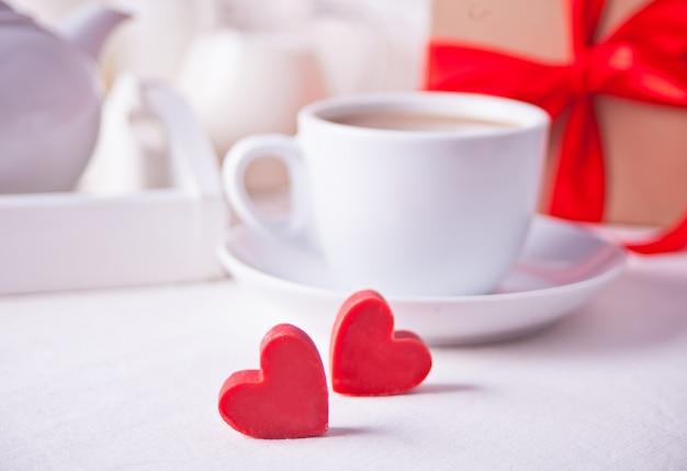 Xícara de café e um coração em forma de bombons de chocolate vermelhos com caixa de presente na mesa branca
