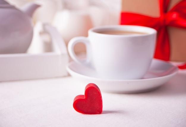 Xícara de café e um coração em forma de doce de chocolate vermelho com caixa de presente na mesa branca