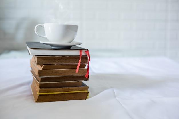 Xícara de café e um livro em uma cama. copo branco com café em um livro. fechar-se