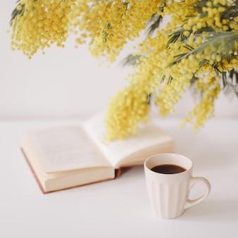 Xícara de café e um livro na mesa branca com buquê de flores amarelas mimosa.