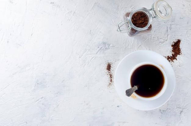 Xícara de café e uma jarra de vidro com pó de café