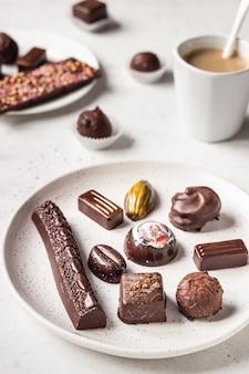 Xícara de café e variedade de bombons de chocolate bem no fundo de pedra cinza.