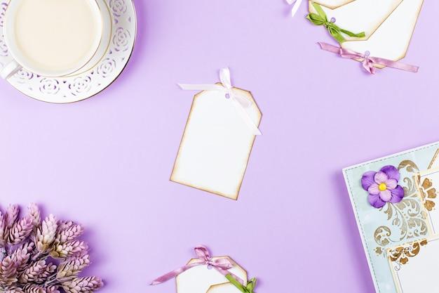 Xícara de café elegante, caderno e folhas de papel plana leigos. fundo feminino em tons pastel. vista do topo