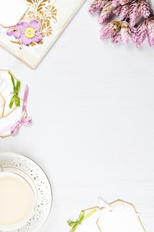 Xícara de café elegante, caderno e folhas de papel plana leigos. fundo feminino em tons pastel.