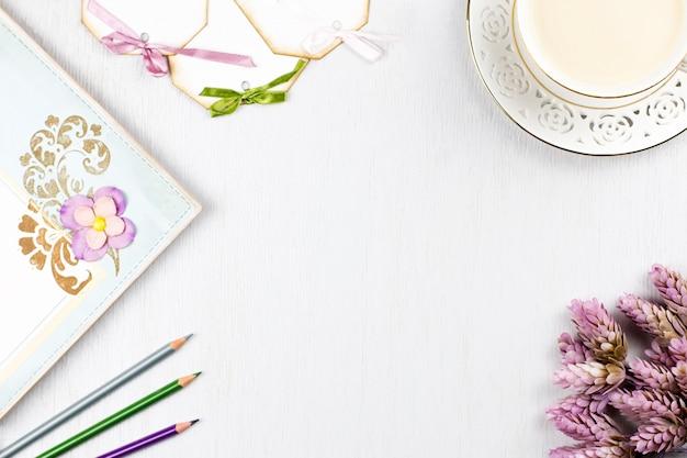 Xícara de café elegante, caderno, etiquetas de papel e flores plana leigos. fundo feminino em tons pastel. vista do topo