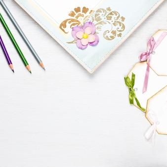 Xícara de café elegante, caderno, etiquetas de papel e flores plana leigos. fundo feminino em tons pastel.