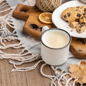 Xícara de café em ângulo alto com biscoitos e cobertor