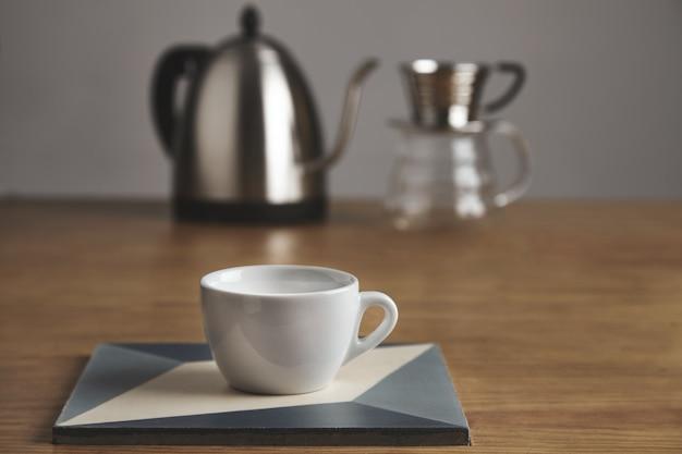 Xícara de café em branco branca na frente do bule moderno e bela cafeteira de gotejamento transparente. copo na placa cerâmica na mesa de madeira grossa na loja de café.