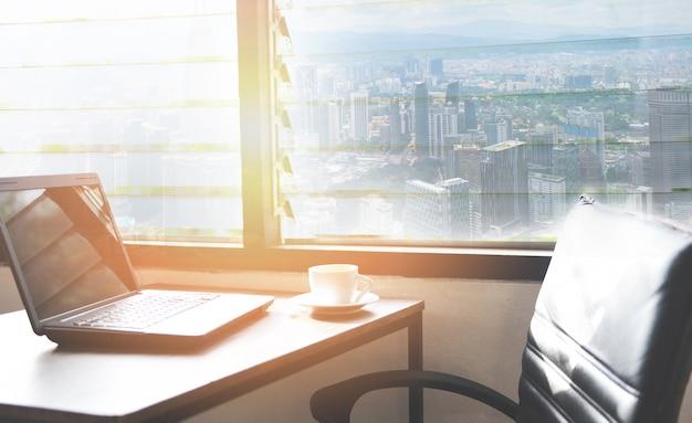 Xícara de café em cima da mesa em um escritório com laptop na mesa no escritório