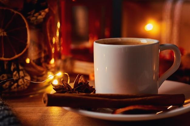Xícara de café em decorações festivas com uma guirlanda de fadas luzes