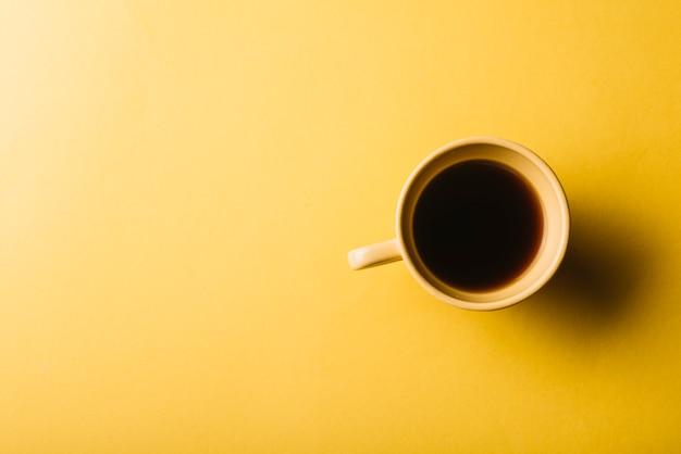 Xícara de café em fundo amarelo