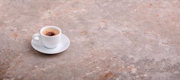 Xícara de café em fundo cinza única xícara de café com creme e gotas de chocolate