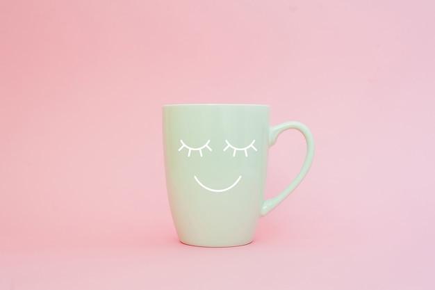 Xícara de café em fundo rosa com cara de sorriso feliz