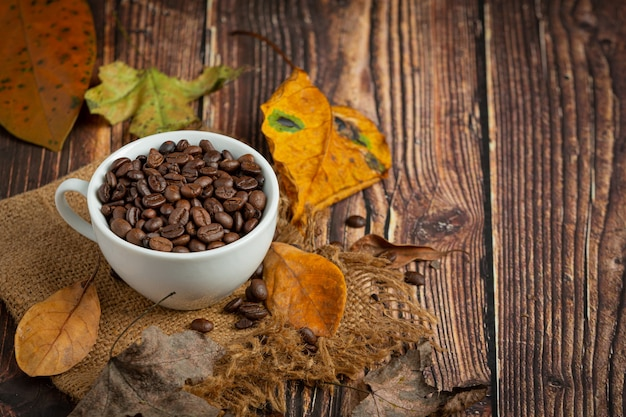 Xícara de café em grão e folhas secas no chão de madeira, olá conceito de setembro.