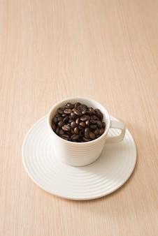 Xícara de café em grão na superfície da madeira