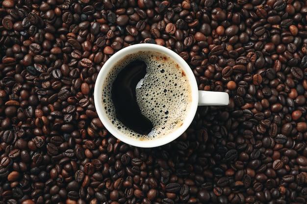 Xícara de café em grãos de café fundo, vista superior