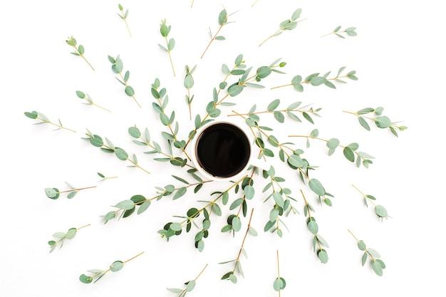 Xícara de café em moldura de galho de eucalipto