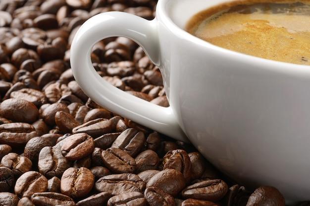 Xícara de café em muito fundo de grãos de café. tiro macro de grãos de café em torno da xícara de café quente.