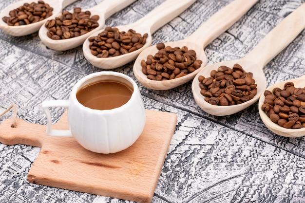 Xícara de café em pouco placa de madeira grãos de café em colher de pau na superfície de madeira