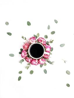 Xícara de café em quadro de botões de flores de rosa cor de rosa e galhos de eucalipto em fundo branco. camada plana, vista superior