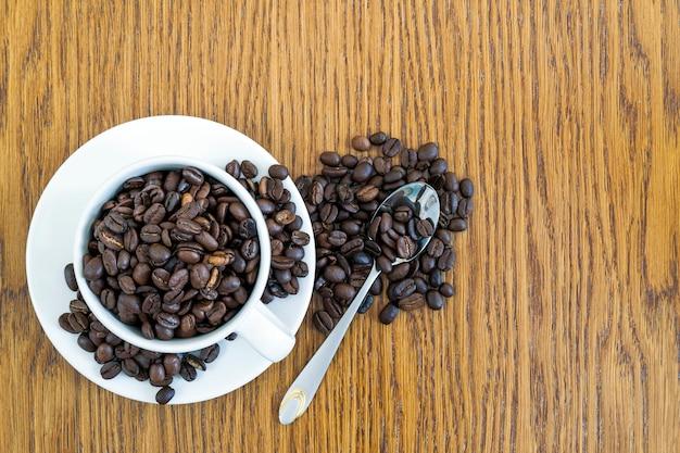 Xícara de café em um copo branco e em feijões de café no fundo de madeira da tabela, vista superior.