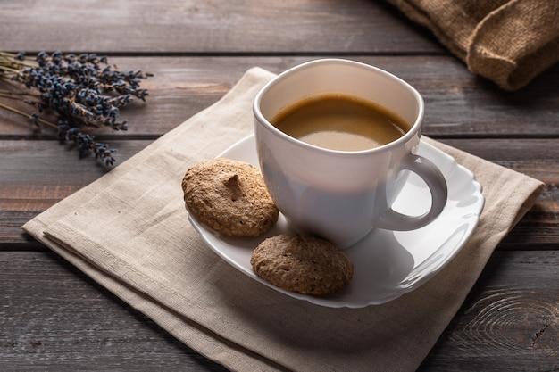 Xícara de café em um guardanapo de linho, grãos de café e visão horizontal do saco