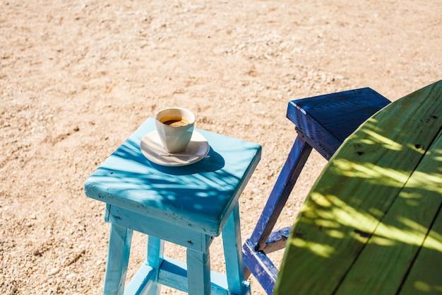 Xícara de café em uma cadeira na praia em um café