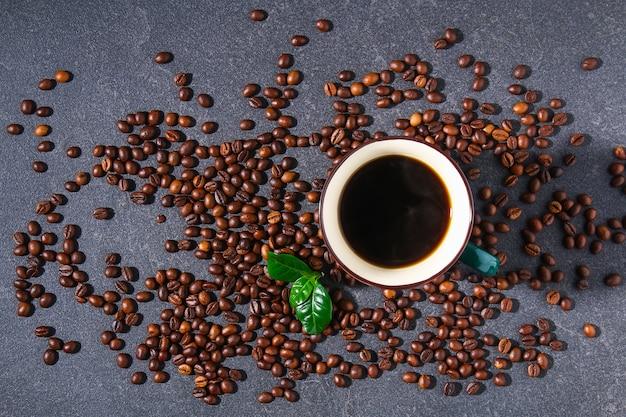 Xícara de café em uma mesa cinza com grãos de café e folhas de café