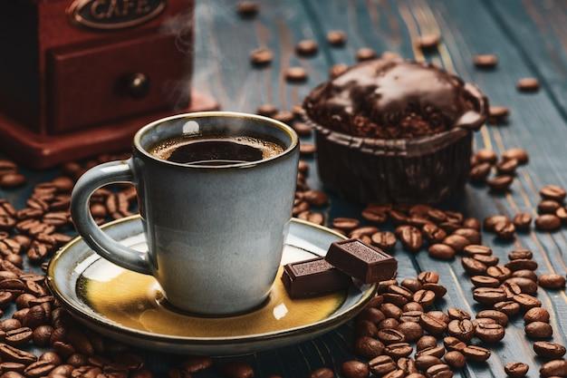 Xícara de café em uma mesa de madeira azul com grãos de café e chocolate