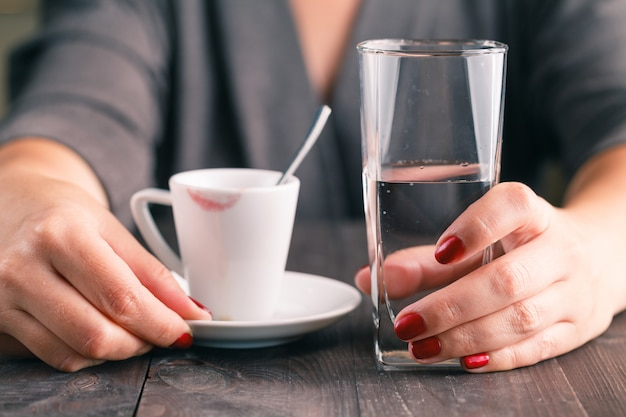 Xícara de café em uma mesa de madeira com copo de água nas mãos de mulher