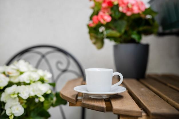 Xícara de café em uma mesa na aconchegante varanda com flores. zona de conforto. jardinagem doméstica. conceito de redução de estresse
