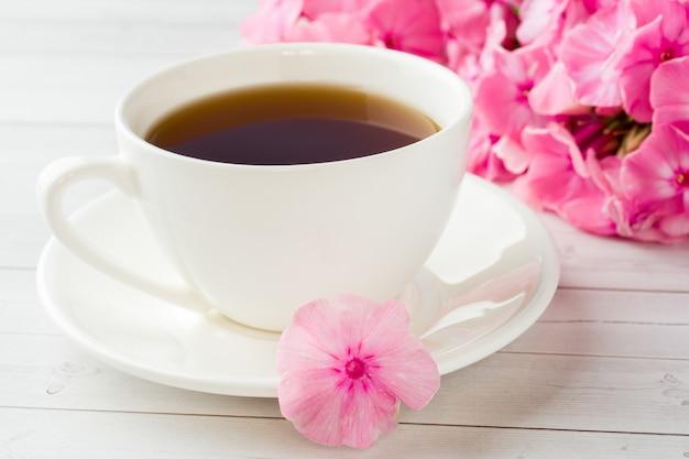 Xícara de café em uma tabela e em umas flores brancas do flox cor-de-rosa.
