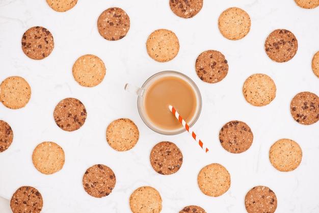 Xícara de café entre o padrão de vários biscoitos de shortbread e aveia com cereais e passas em fundo preto de madeira. vista superior, configuração plana.