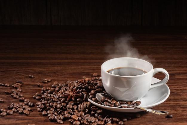 Xícara de café esfumaçado com colher em grãos de café