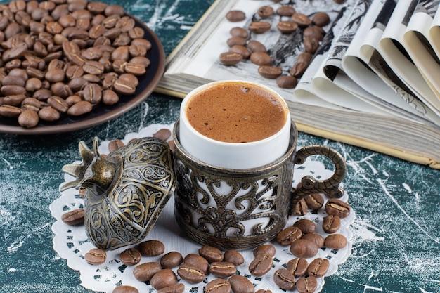 Xícara de café espumoso, prato de grãos de café e livro sobre a mesa de mármore.
