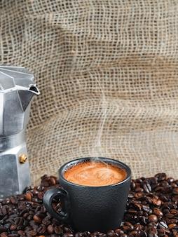 Xícara de café expresso aromático forte com espuma entre os grãos de café torrados, ao lado de uma cafeteira