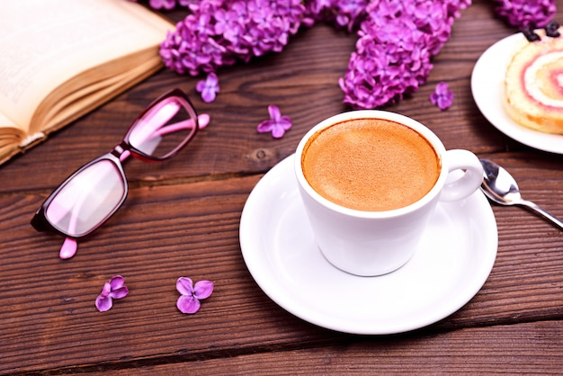 Xícara de café expresso, atrás de um livro aberto