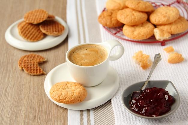 Xícara de café expresso com biscoitos de coco em um prato