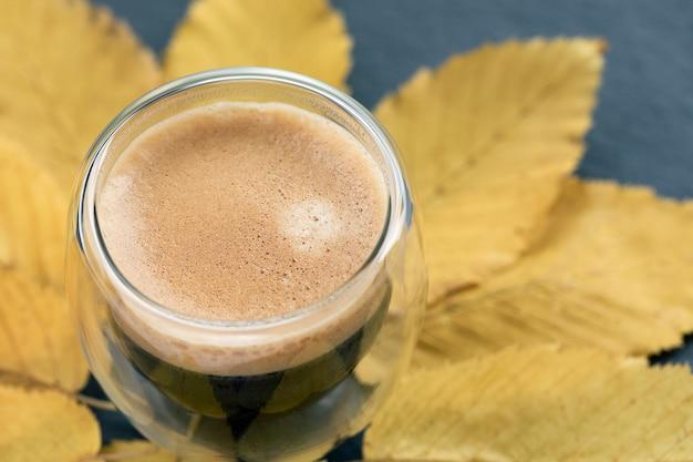 Xícara de café expresso com creme e folhas amarelas de outono em fundo preto clima de outono layout de outono