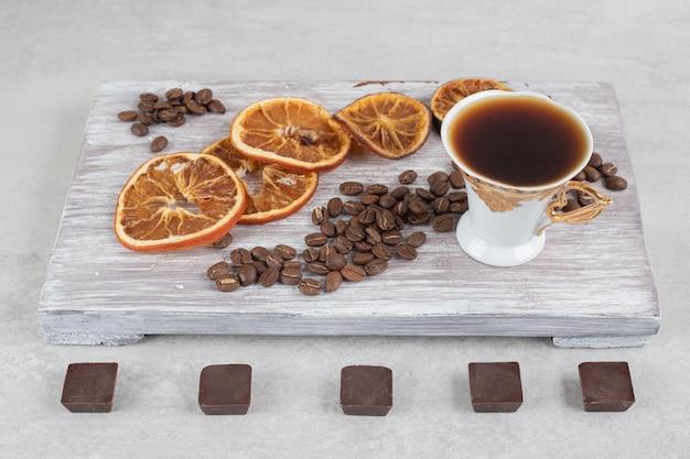 Xícara de café expresso com fatias de chocolate e laranja na placa de madeira