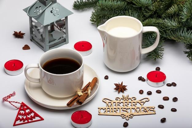 Xícara de café expresso com leite, árvores de natal, lanterna, velas vermelhas e texto de madeira feliz natal